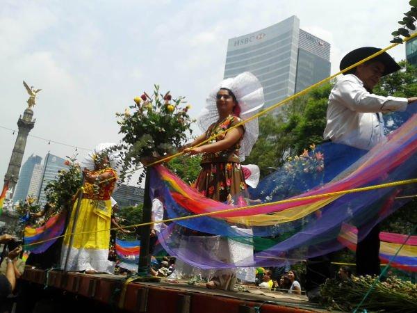 En un carro que lleva la bandera arcoíris como banda de seguridad ellos vestidos con traje típico sonríen y saludan al pasar ante los espectadores.