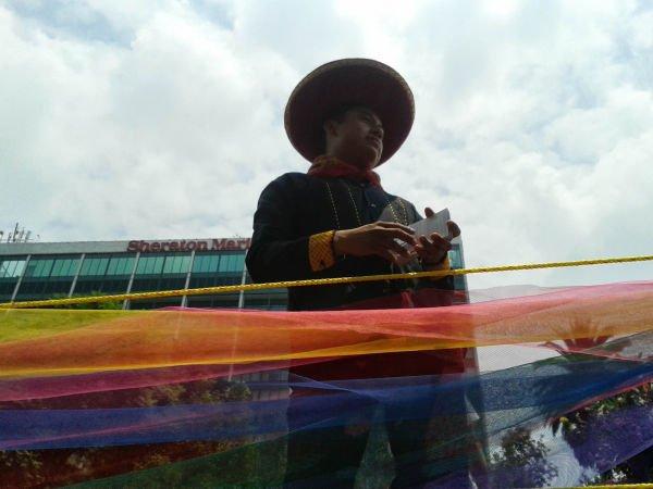 En un carro adornado con la bandera Living, vestido con traje tipico sonríe al pasar.